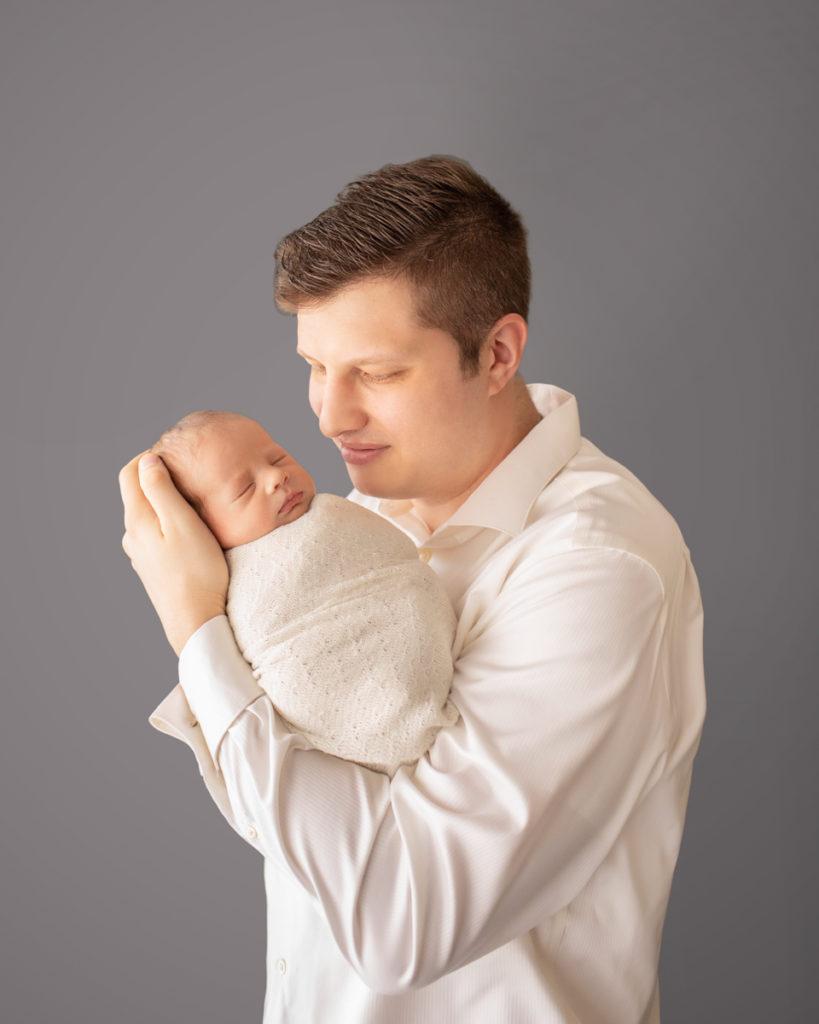 Dad looking gazing and cuddling newborn baby Rowan dressed in white against grey Gainesvile Florida Photos