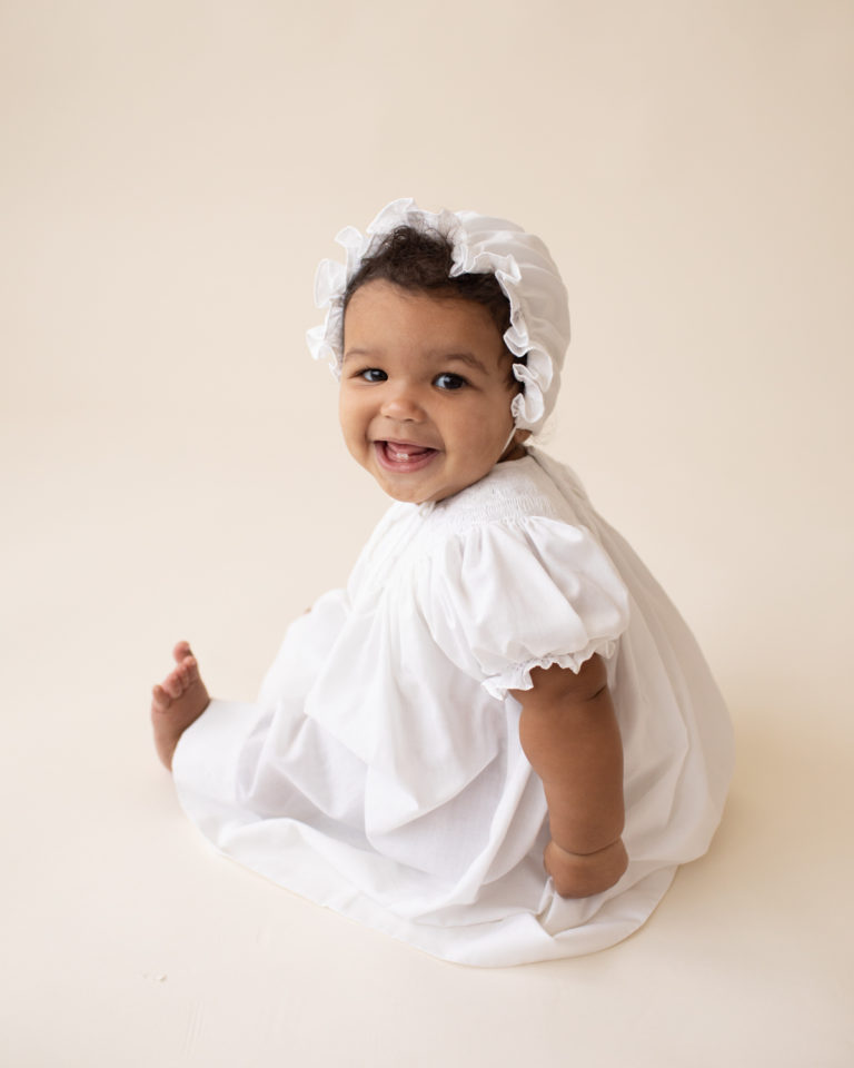Baby 6 months old smiling sitting up in white cotton dress and matching bonnet Gainesville FL