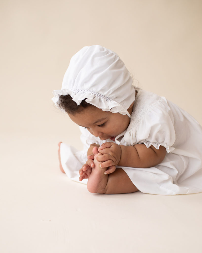 Baby 6 months old sitting up reaching for toes dressed in white cotton dress and matching bonnet Gainesville FL