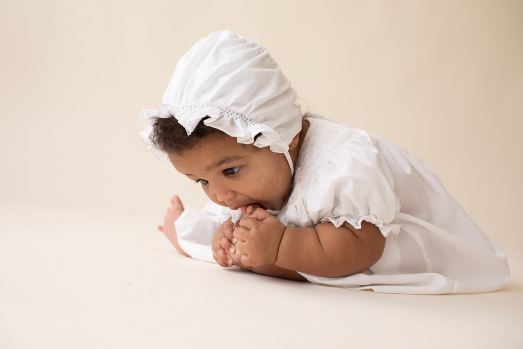 Baby 6 months old sitting up sucking her toes dressed in white cotton dress and matching bonnet Gainesville FL