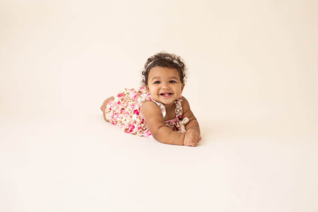 Baby 6 months old smiling pushing up on white floor dressed in pink floral jumper in Gainesville FL