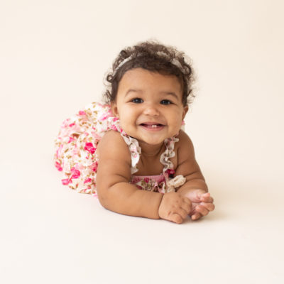 Baby 6 months old smiling pushing up on elbows on white floor dressed in pink floral jumper in Gainesville FL