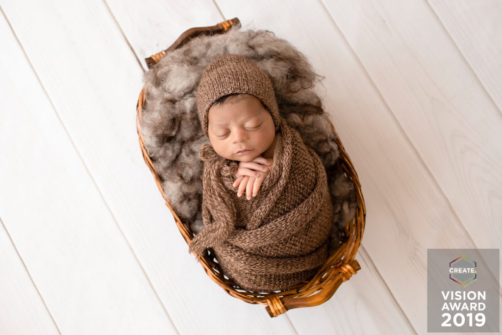 Award winning newborn photography baby wrapped in bown knit bundle lying in basket with brown fur