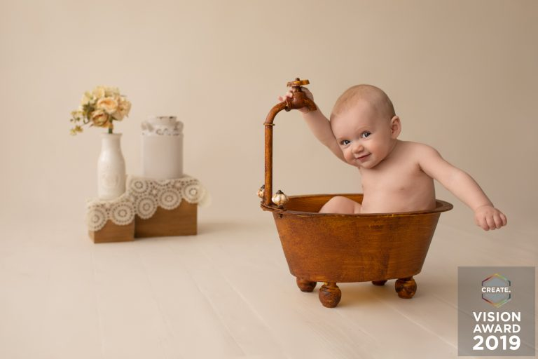 Award winning newborn photography baby posed in brown vintage tub with a teasing smile at floral and lace accents against ivory background