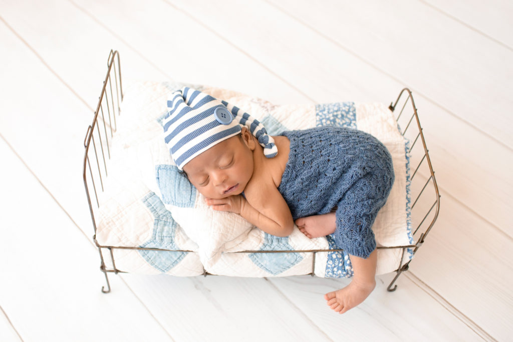 Newborn Jacob photos in blue knit overalls with a striped sleepy hat posed on quilt covered metal bed Gainesville FL