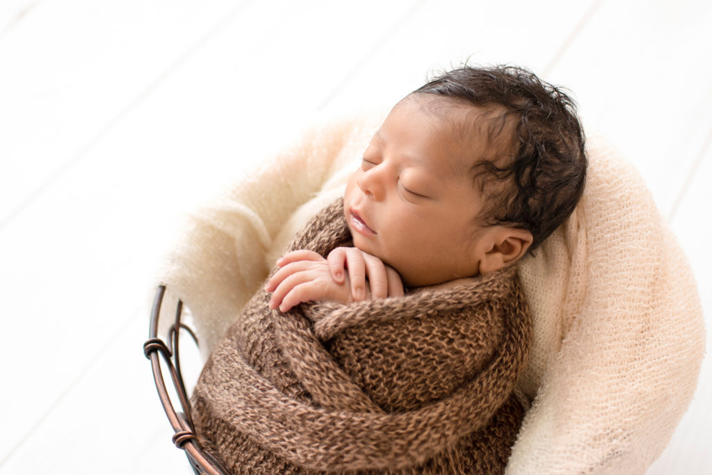 Newborn Jacob photos with full head of hair profile wrapped in knit brown wrap potato sack in metal basket against cream wood floor Gainesville FL