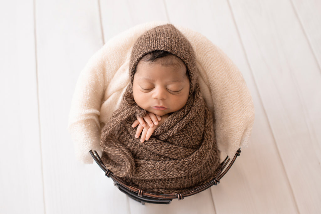 Newborn Jacob photos with full head of hair wrapped in knit brown wrap potato sack in metal basket against cream wood floor Gainesville FL