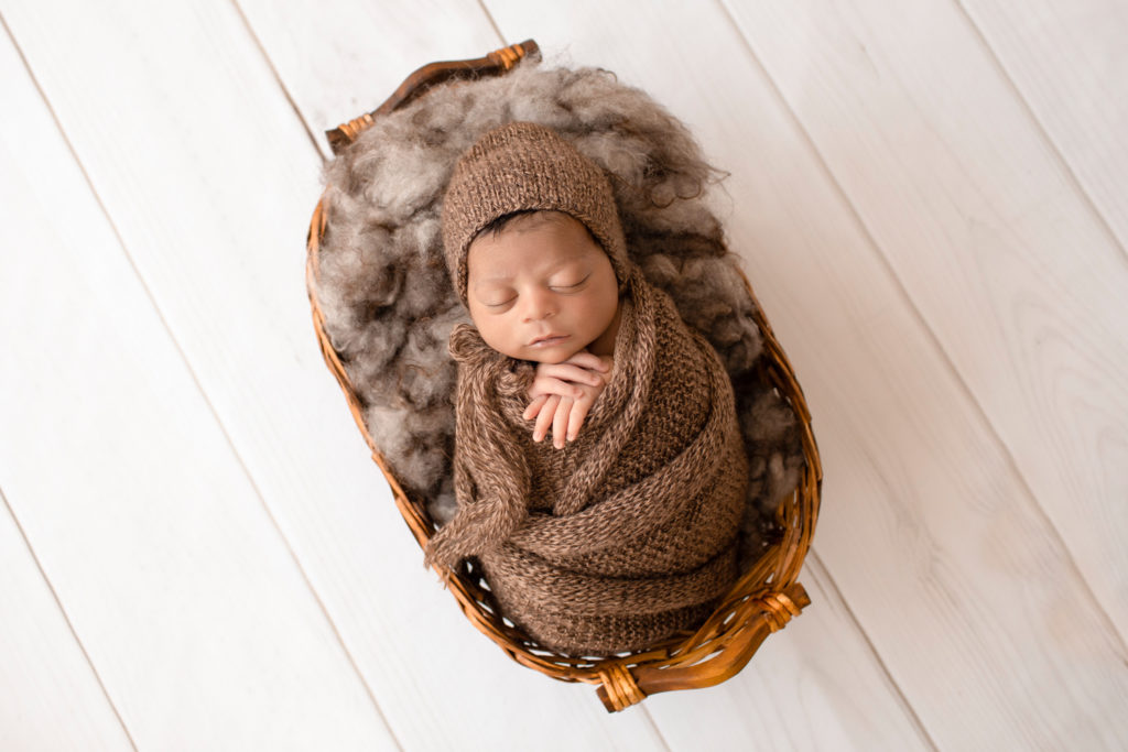 Newborn Jacob photos with full head of hair wrapped in knit brown wrap potato sack on brown fur in basket Gainesville FL