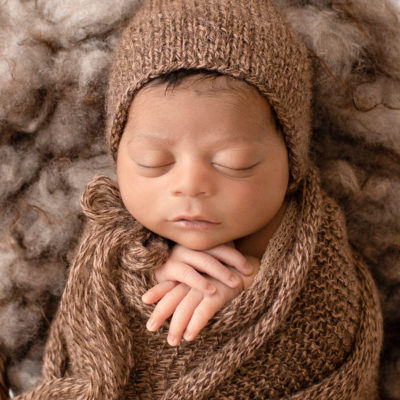 newborn pictures Jacob face close up with full head of hair wrapped in knit brown wrap potato sack on fur stuffed brown basket Gainesville FL