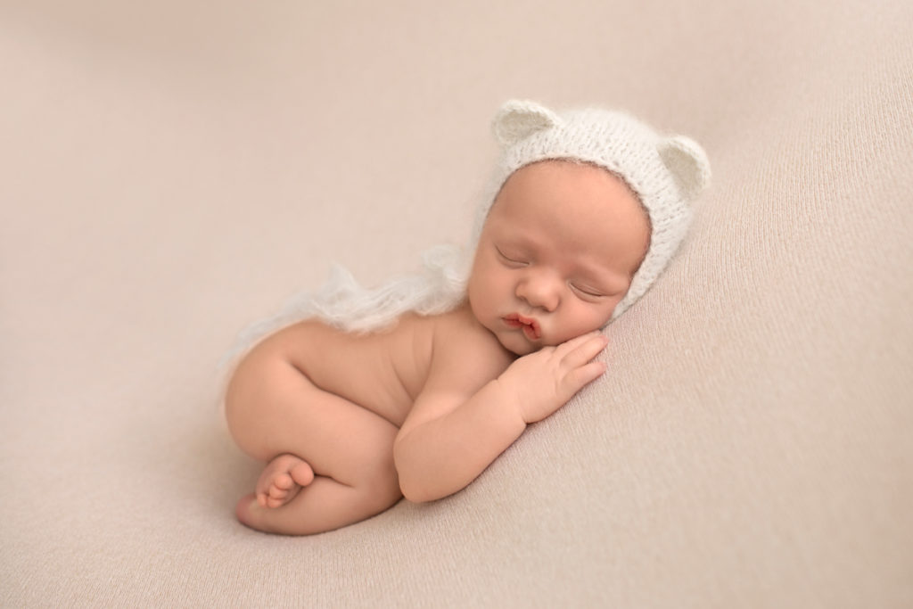 Gainesville Newborn Boy Gavin naked pose on beige blanket with bottom up and white bear hat Andrea Sollenberger Photography