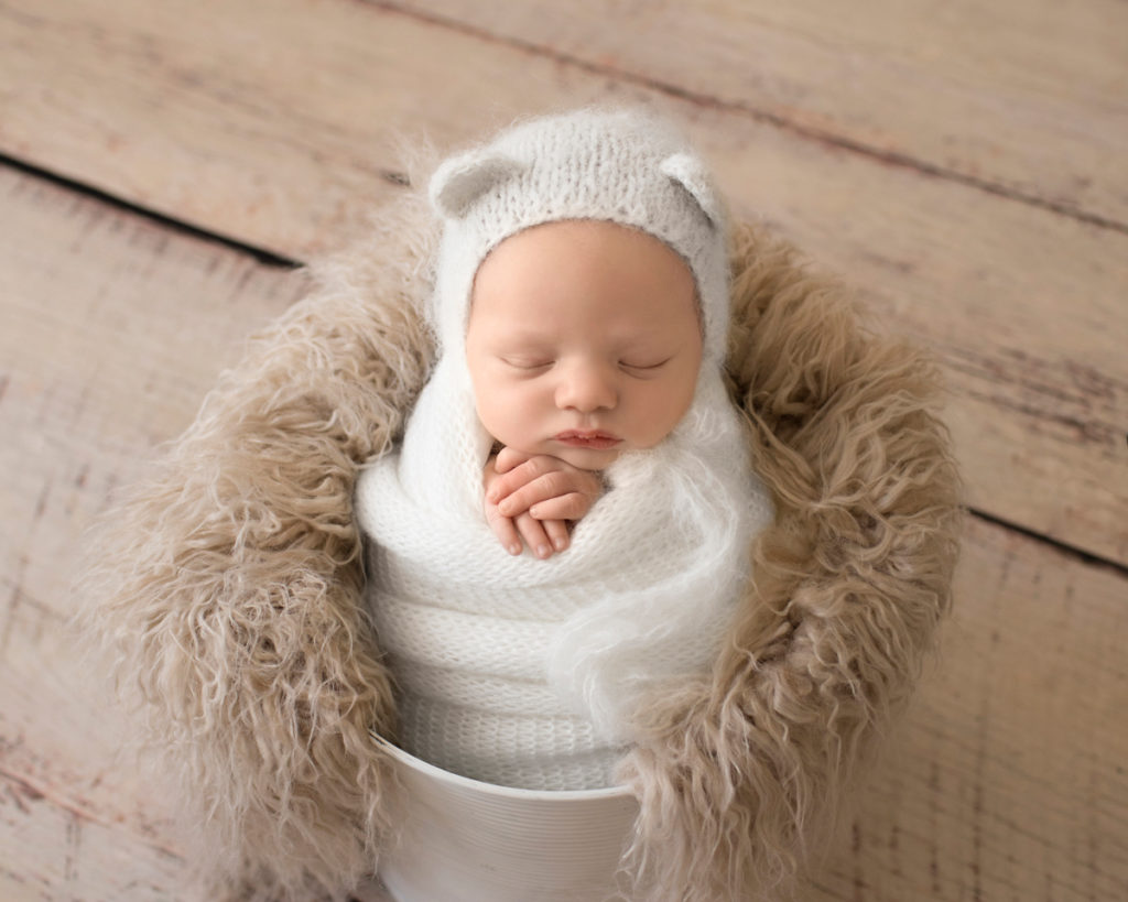 Gainesville Newborn Boy Gavin white knit wrap potato sack and bear hat in white bucket stuffed with beige fur Andrea Sollenberger Photography