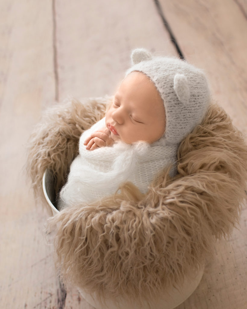 Gainesville Newborn Boy Gavin white knitted wrap potato sack and white knitted bear bonnet in white bucket stuffed with beige fur profile shot Andrea Sollenberger Photography