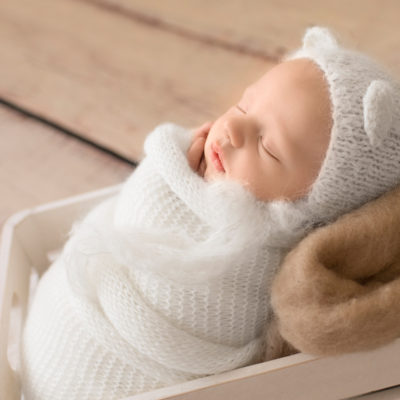 Gainesville Newborn Boy Gavin profile photo potato sack white knit wrap and bear hat on beige blanket in white crate