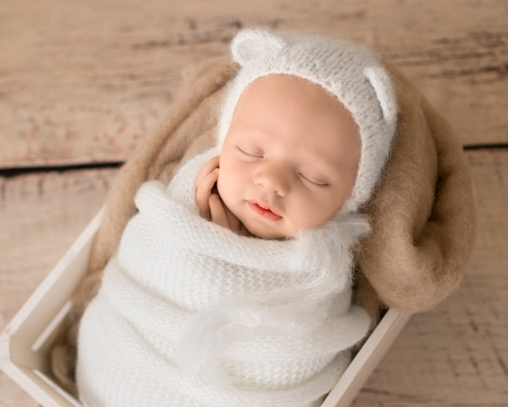 Gainesville Newborn Boy Gavin potato sack white knit wrap and bear hat on beige blanket in white crate Andrea Sollenberger Photography