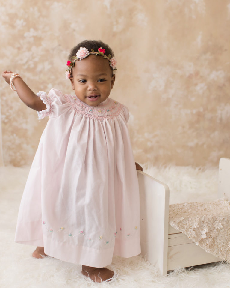 Rose One Year Old Baby Photos standing with pink smocked dress and floral crown pearls and ivory lace Gainesville Florida