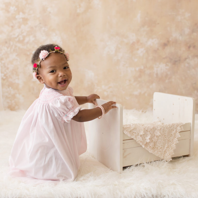 Rose One Year Old Baby Photos smiling with pink smocked dress and floral crown pearls and ivory lace pink and peach tones Gainesville Florida