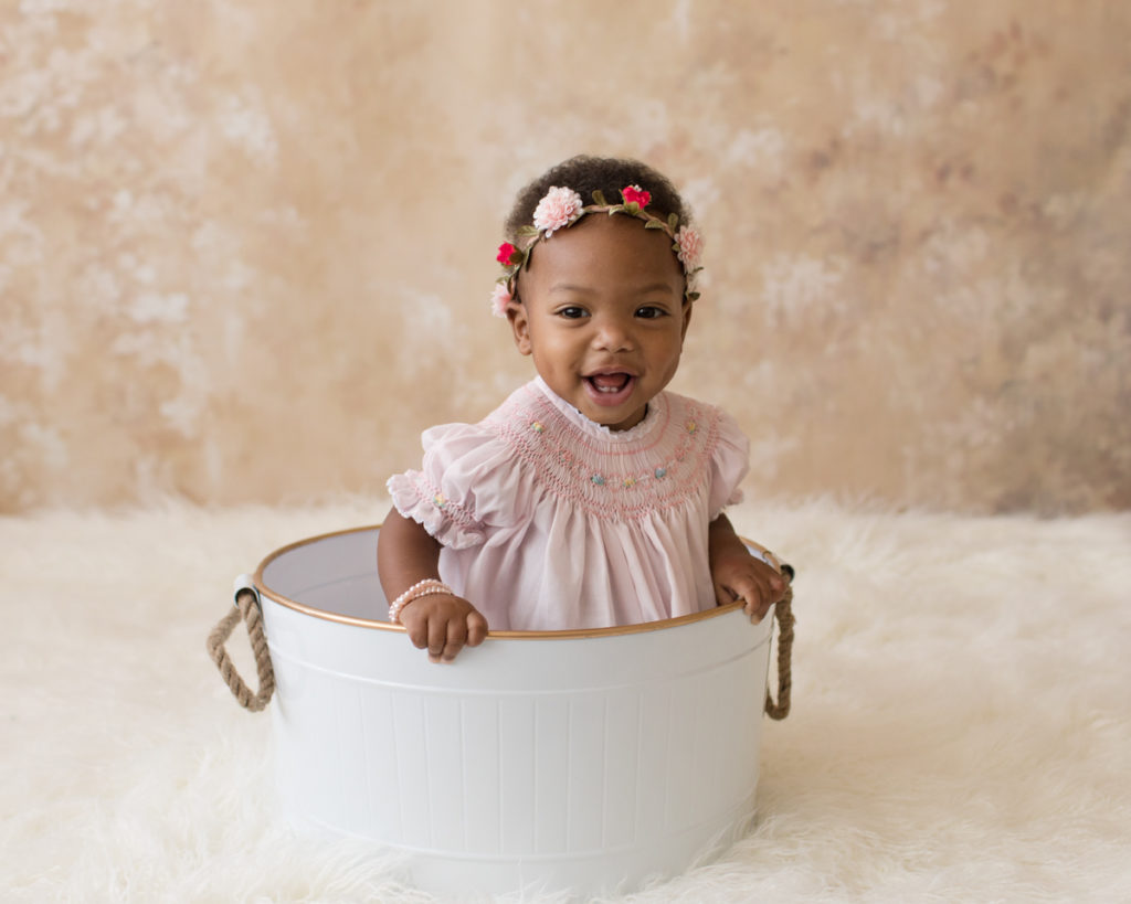 Rose One Year Old Baby Photos sitting in white tub with pink smocked dress and floral crown pearls pink and peach tones Gainesville Florida