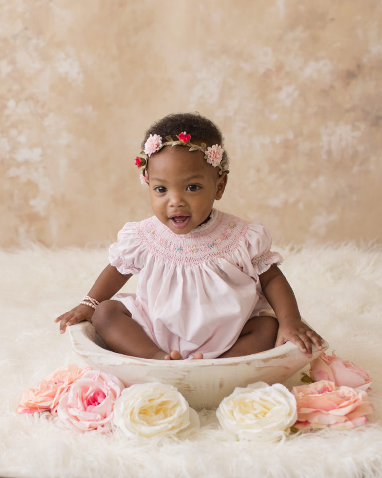 Rose One Year Old Baby Photos pink and peach tones sitting in white antiqued wooden bowl with pink smocked dress and floral crown pearls Gainesville Florida
