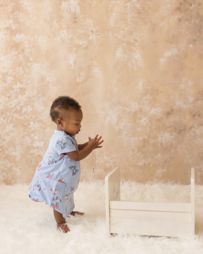 Rose One Year Old Baby Photos pink and peach tones standing alone with blue dress Gainesville Florida