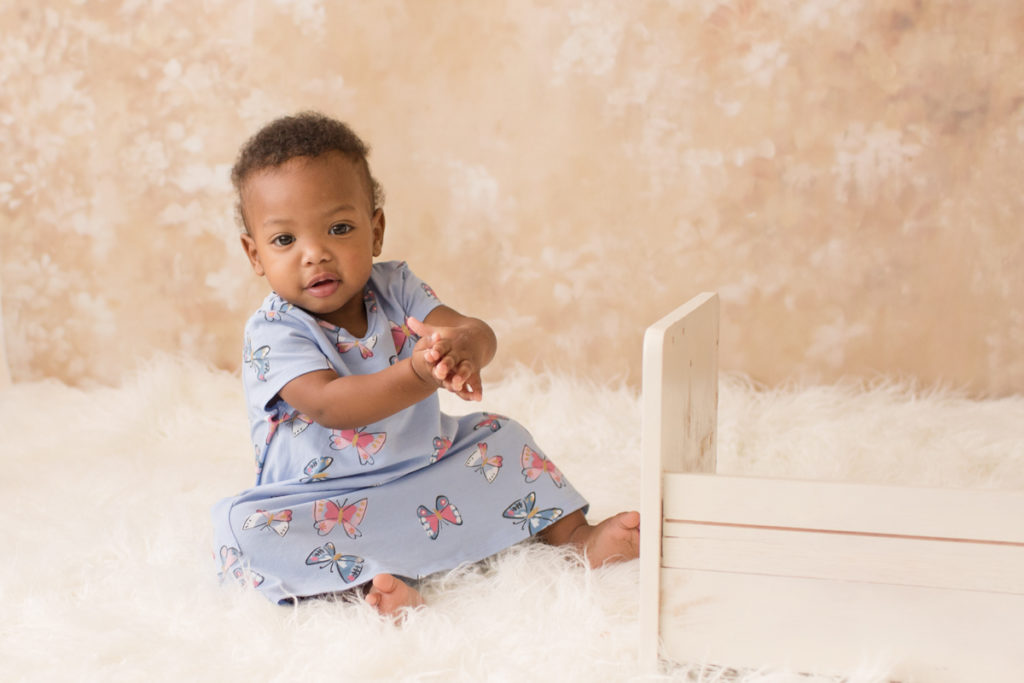 Rose One Year Old Baby Photos pink and peach tones sitting and clapping with blue dress Gainesville Florida