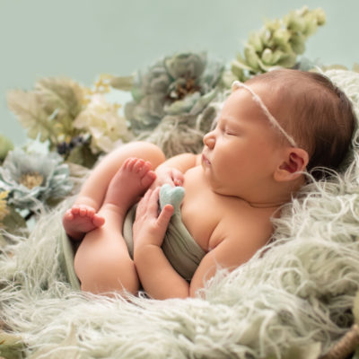 Hensley newborn photos sleeping in round basket fur textured surrounded with shades of green flowers profile close up baby hands holding tiny felted green heart Gainesville Florida Newborn Photography