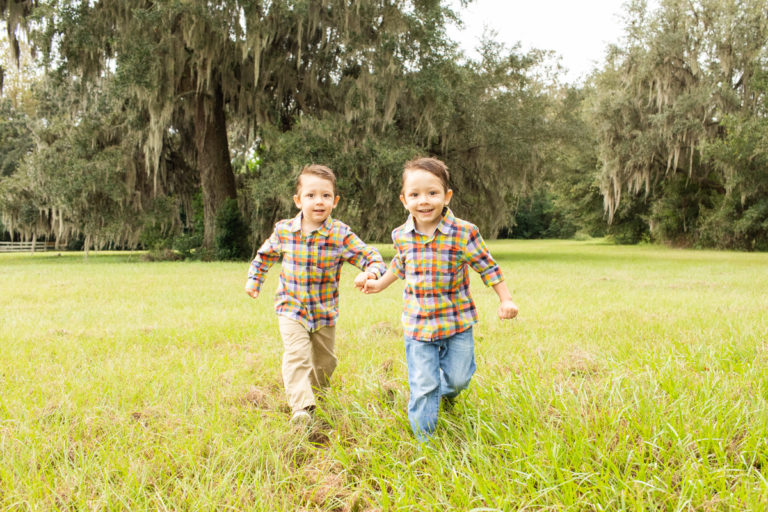 Family Photos Three Year Old Twin Boys hand in hand running through field at Horseshoe Farm Alachua Florida