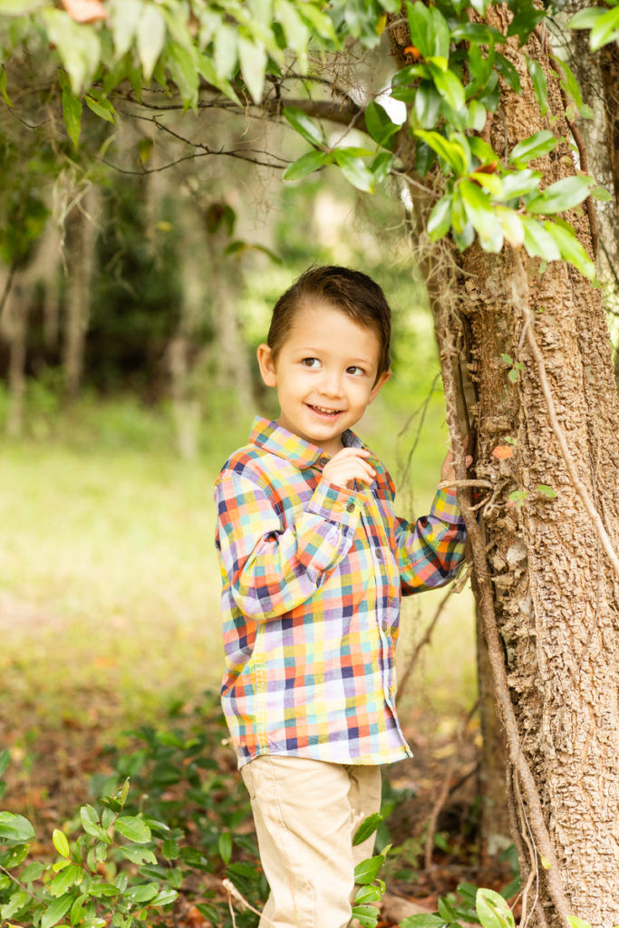 Three Year Old Boy with shy grin leaning against tree fall photos Horseshoe Farm Alachua Florida