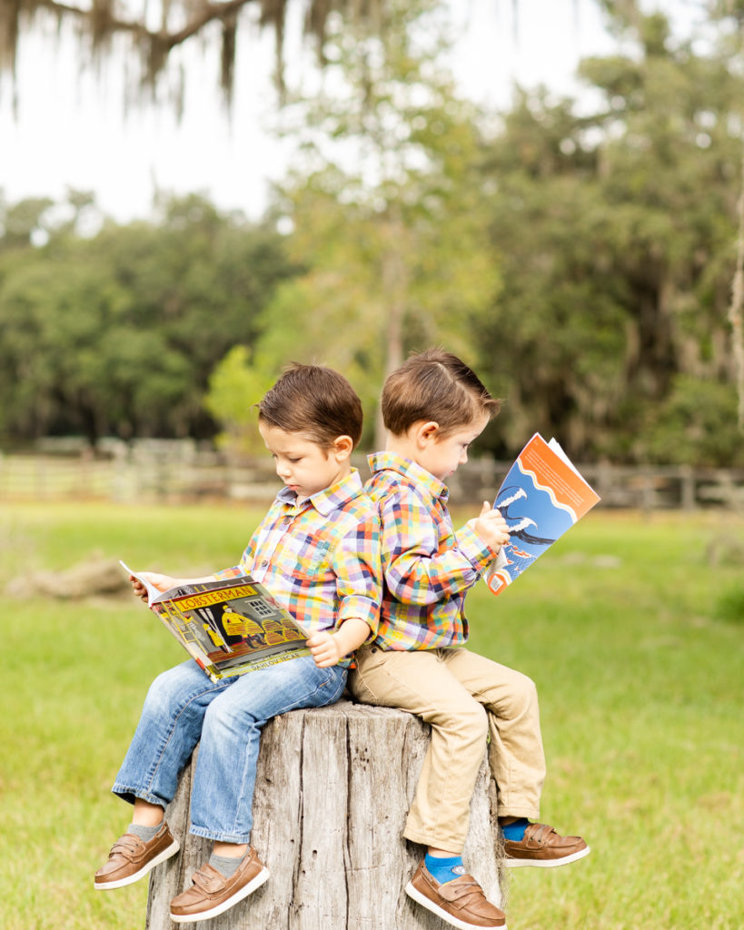 Family Photos Three Year Old Twin Boys reading books on tree stump at Horseshoe Farm Alachua Florida