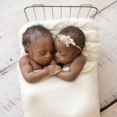 Twin Newborns Samuel and Sophia posed cuddling holding hands in metal newborn bed covered with cream blanket textured pillow distressed white floor in Gainesville Florida newborn photos taken from above