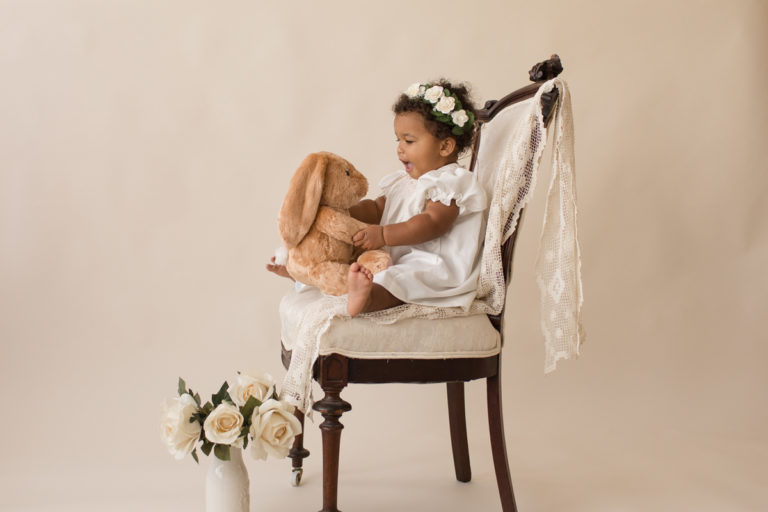 One year old Sara sitting with stuffed bunny on ivory victorian chair with lace smocked white dress milestone session Gainesville Florida