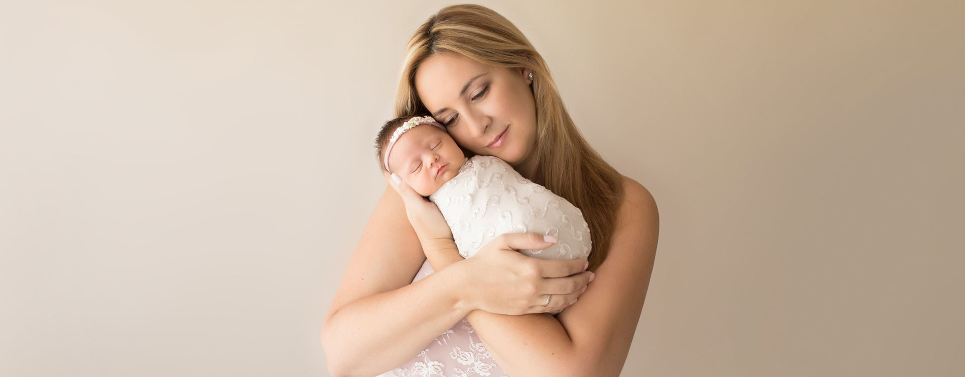 Gorgeous Mom in pink lace cuddling newborn girl wrapped in lace cream photos Gainesville FLorida