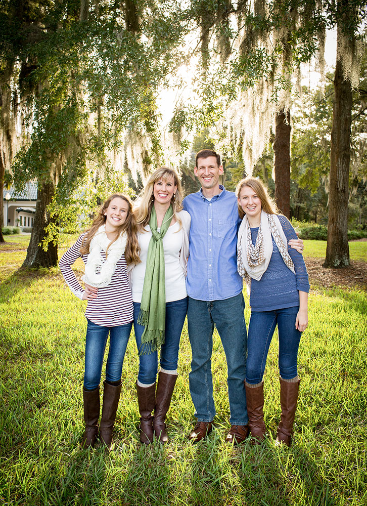 Family with teens in denim sweathers boots with sun flare through moss on trees Gainesville Florida photos