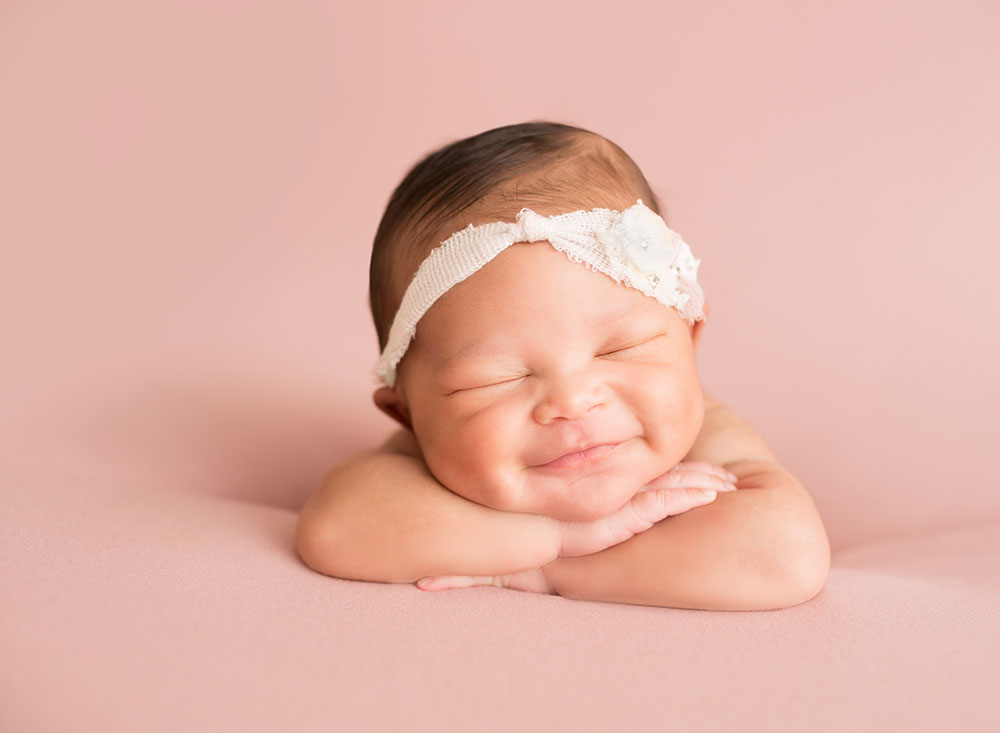 Baby girl grins propped up on arms in Newborn Photo session on Soft Pink Baby Blanket Gainesville FLorida