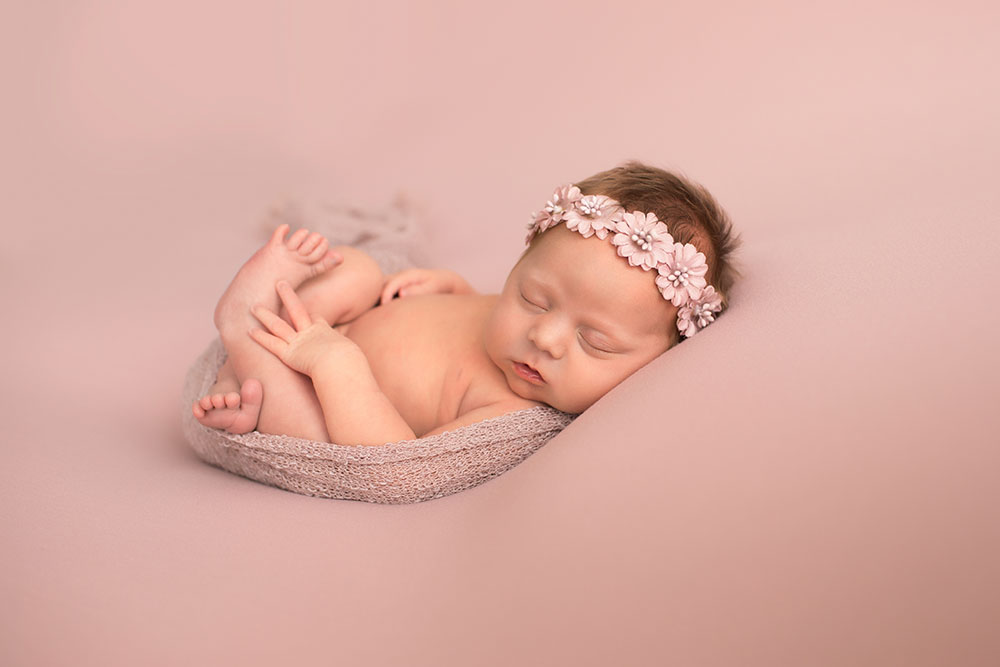 Newborn naked baby girl wrapped in pink on blush blanket with floral crown on head photos Gainesville FLorida