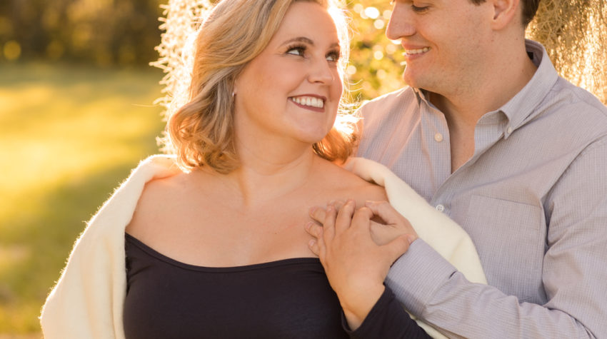 Maternity couple outdoors framed by moss draped sun lit tree Katie in navy blue maternity gown with white shawl and husband Ben in denim and grey Gainesville Florida Maternity portraits