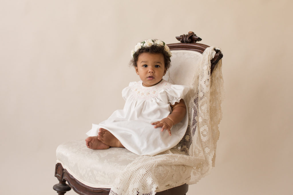 One year baby pictures Sara wearing white heirloom smocked dress and white floral crown posed sitting on lace draped elegant ivory chair with cream background Gainesville Florida Baby Photography