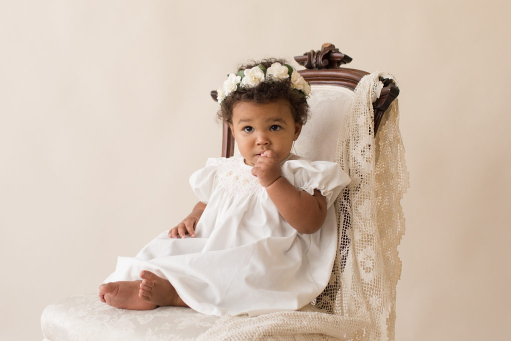 One year baby pictures Sara wearing white heirloom smocked dress and white floral crown shy look posed sitting on lace draped elegant ivory chair with cream background Gainesville Florida Baby Photography