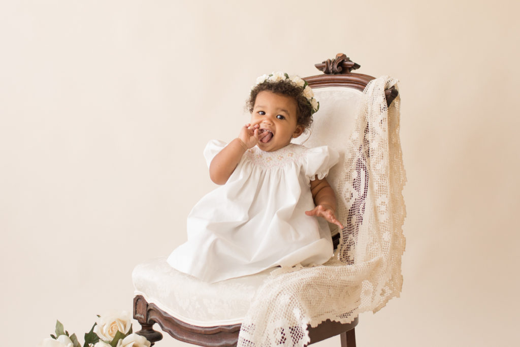 One year baby pictures Sara wearing white heirloom smocked dress and white floral crown sucking fingers smiling posed sitting on lace draped elegant ivory chair with cream background Gainesville Florida Baby Photography
