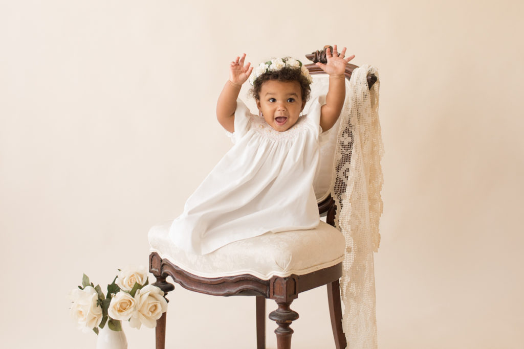 One year baby pictures Sara wearing white heirloom smocked dress and white floral crown excited happy arms straight up in air posed sitting on lace draped elegant ivory chair with white roses cream background Gainesville Florida Baby Photography