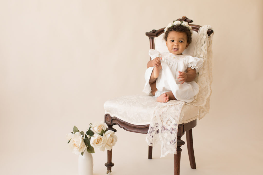 One year baby pictures Sara wearing white heirloom smocked dress and white floral crown excited holding foot posed sitting on lace draped elegant ivory chair with white roses cream background Gainesville Florida Baby Photography