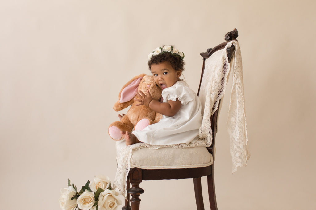 One year baby pictures Sara wearing white heirloom smocked dress and white floral crown excited hugging stuffed bunny posed profile sitting on lace draped elegant ivory chair with white roses cream background Gainesville Florida Baby Photography