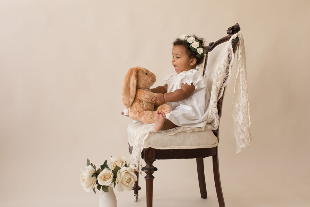 One year baby pictures Sara wearing white heirloom smocked dress and white floral crown excited talking to stuffed bunny posed sitting profile on lace draped elegant ivory chair with white roses cream background Gainesville Florida Baby Photography