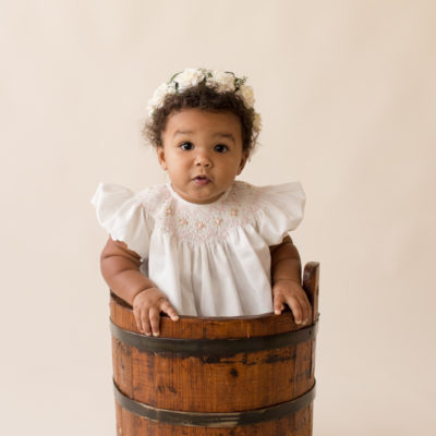 One year baby pictures Sara big brown eyes and baby rolls wearing white heirloom smocked dress and white floral crown sitting in wooden bucket cream background Gainesville Florida Baby Photography