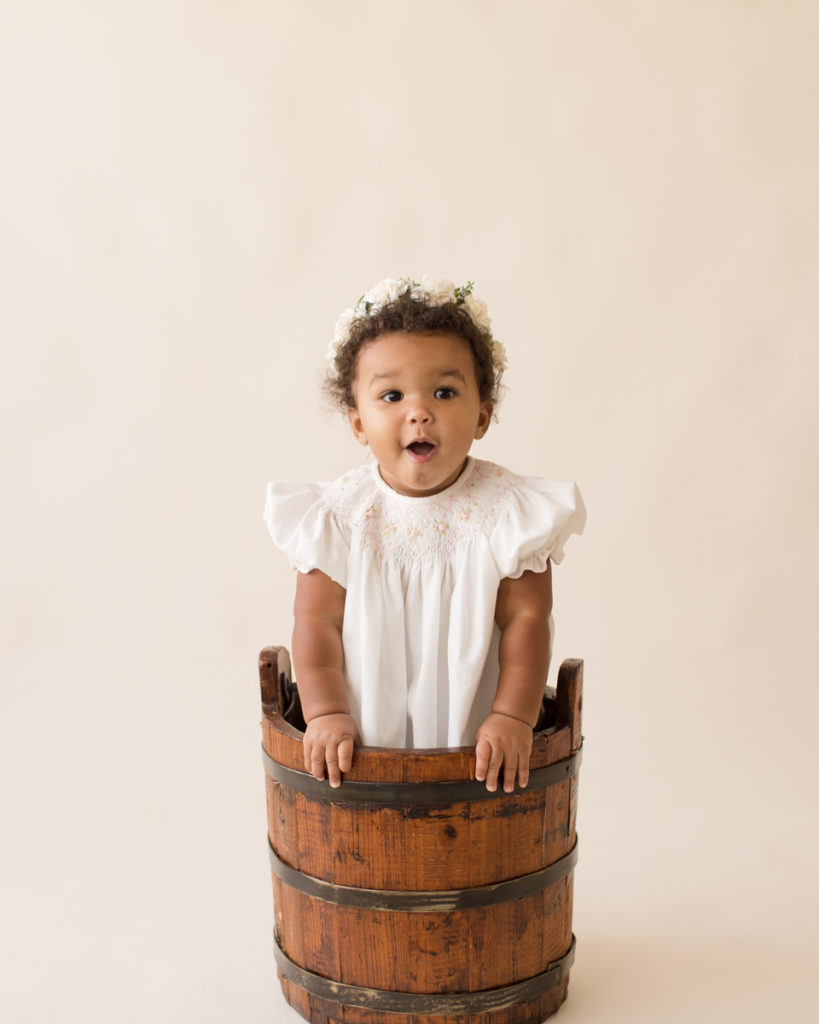 One year baby pictures Sara wearing white heirloom smocked dress and white floral crown standing up in wooden bucket cream background Gainesville Florida Baby Photography