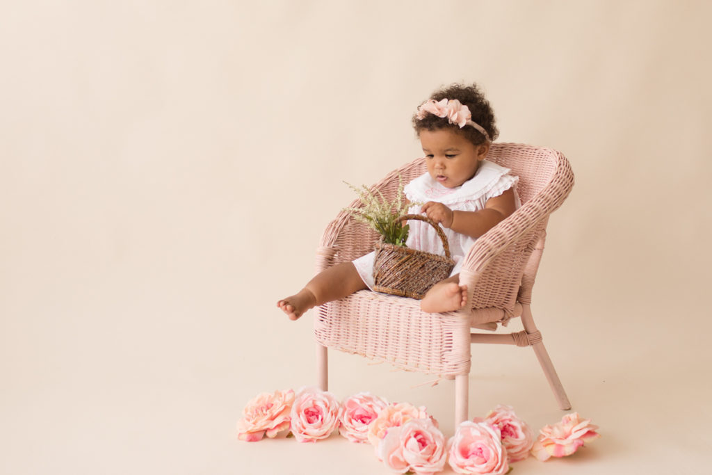 One year baby pictures Sara wearing white heirloom smocked dress and pink floral crown excited holding tiny basket of flowers posed sitting on pink wicker children chair with pink and peach roses cream background Gainesville Florida Baby Photography