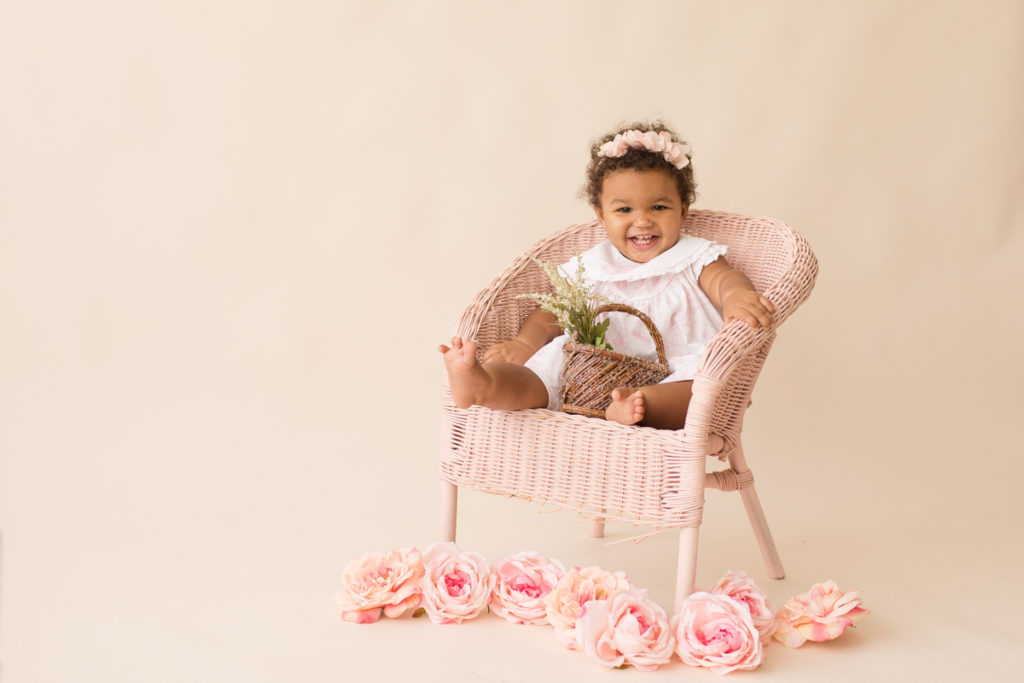 One year baby pictures Sara wearing white heirloom smocked dress and pink floral crown big smile holding tiny basket of flowers posed sitting on pink wicker children chair with pink and peach roses cream background Gainesville Florida Baby Photography
