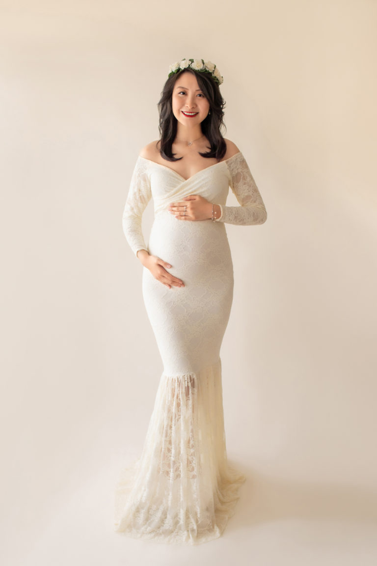 Maternity photo pregnant mom in elegant ivory lace long sleeve fitted gown with circular train wearing ivory floral crown smiling at camera full shot to floor Gainesville Florida