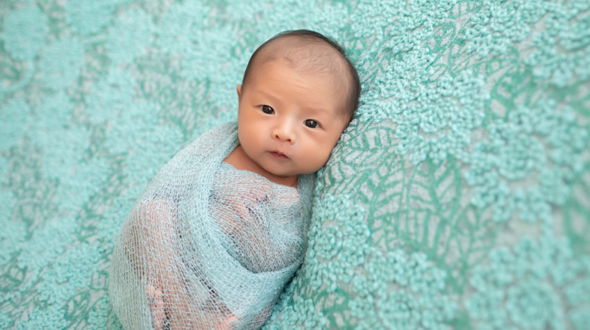 Gainesville newborn portraits baby girl looking straight at camera with her eyes open wrapped in aqua fabric and lying on pale aqua floral blanket