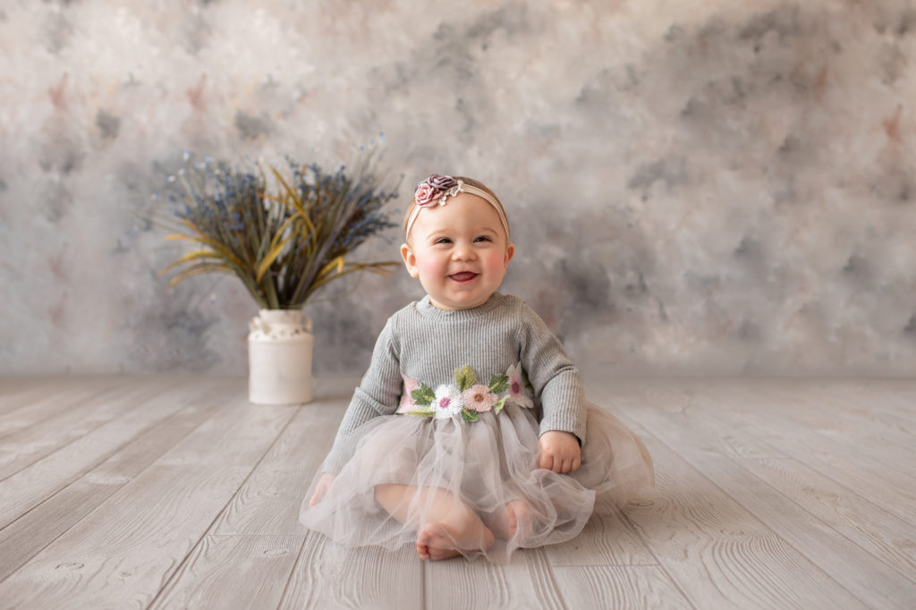 baby photo eight month girl Madison dressed in grey floral dress and pink floral headband with the biggest baby grin sitting by herself on grey floor with floral backdrop Gainesville Florida