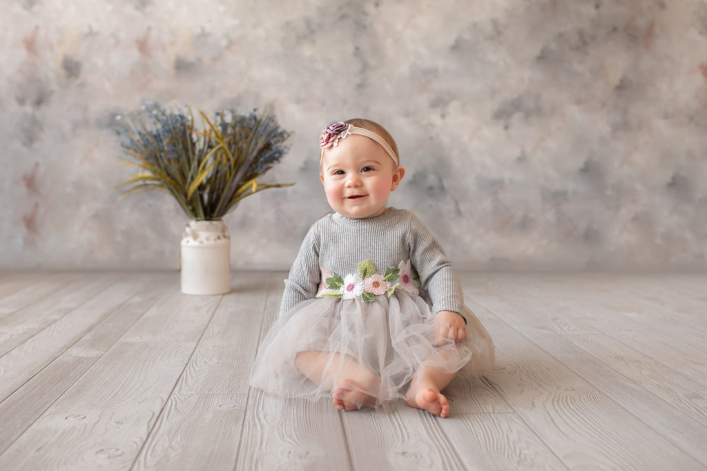 baby photo eight month girl Madison dressed in grey floral dress and pink floral headband smiling and sitting by herself on grey floor with floral backdrop Gainesville Florida